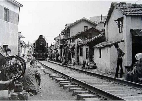 """上世纪八十年代中期,淞沪铁路东宝兴路道口的旧影。沿路筑有棚户房,这里的孩子被戏称为""""铁道游击队的后代""""。(配于《淞沪铁路》一章中).jpg"""