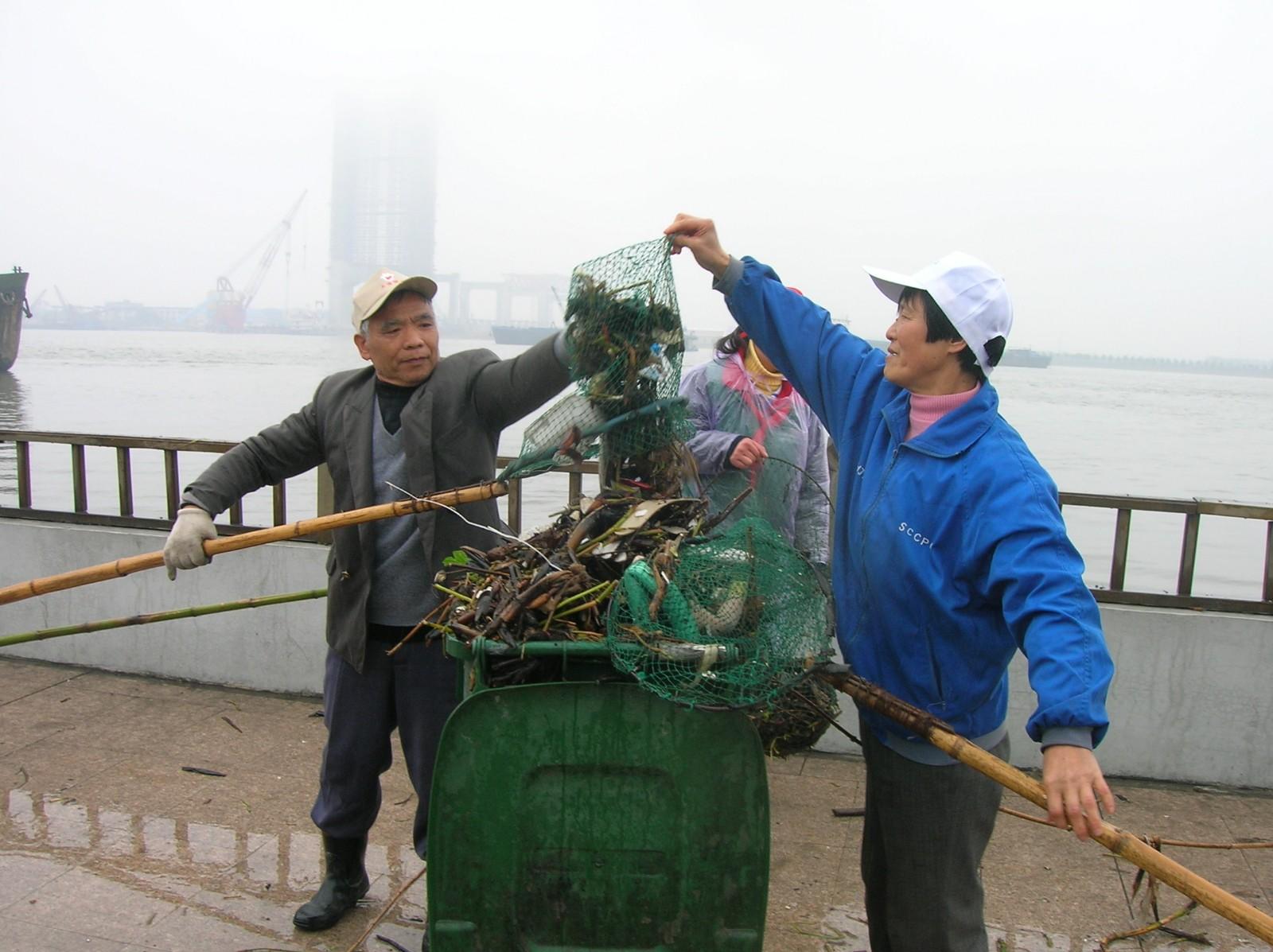 第三代志愿者张更大夫妇打捞垃圾.JPG